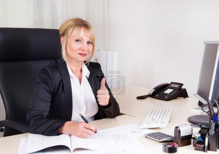 Photo pour Femme d'affaires prospère assise dans son bureau . - image libre de droit