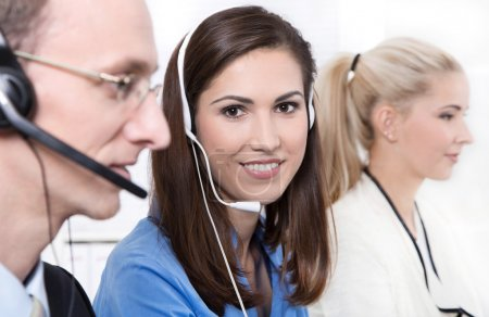 Telesales or helpdesk team - helpful woman with headset smiling