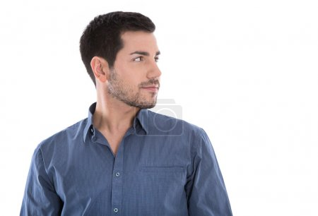 Portrait of handsome young man looking sideways in blue shirt is