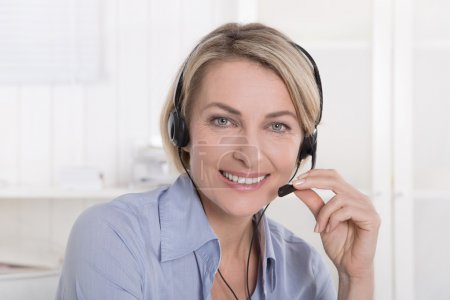 Portrait of smiling blond mature woman working with headphone at