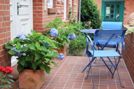 Photo pour Gros plan de la façade de la maison blanche porte, des fleurs et des chaises bleues avec table. - image libre de droit