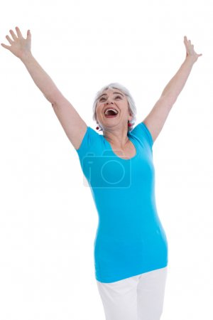 Cheering happy older woman isolated in a blue shirt.