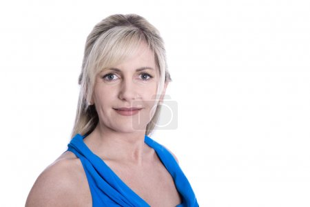 Isolated face of a beautiful middle aged blond woman in blue.