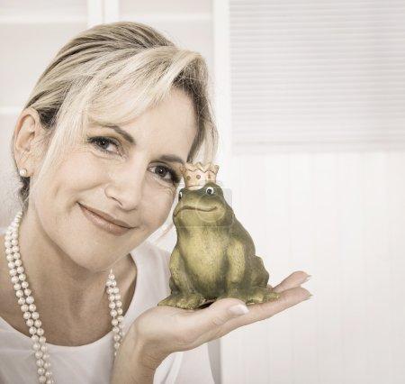 Photo pour Unique attrayant maturer femme embrasser une grenouille roi dans ses mains . - image libre de droit