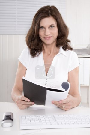Portrait of a senior manager reading balance sheet.
