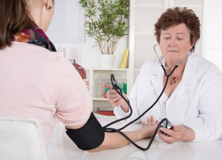 Senior female doctor measuring blood pressure with patient.
