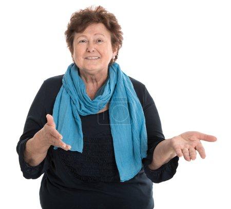 Photo pour Portrait d'une heureuse aînée isolée parlant avec ses mains portant une chemise bleue . - image libre de droit
