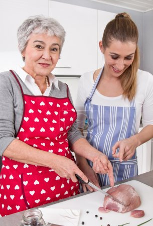 Photo for Mother and daughter preparing meal together: roast pork. - Royalty Free Image
