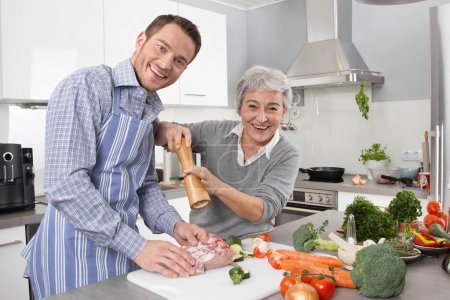 Photo for Young man and older woman cooking together in the kitchen and have fun. - Royalty Free Image