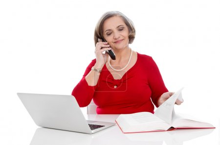 Isolated senior business woman in red calling - sitting at desk.