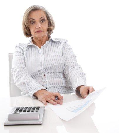 Shocked senior businesswoman looking at increasing costs.