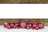 Wooden christmas background with red balls for a greeting card.