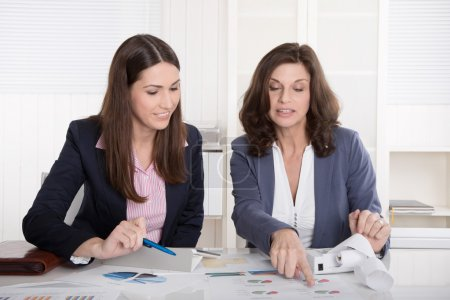 Photo for Two business woman analyzing balance sheet sitting at desk. - Royalty Free Image