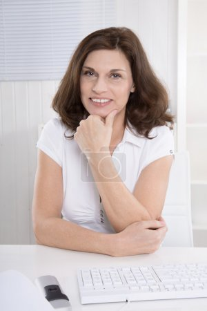 Photo for Portrait of a happy and satisfied older woman sitting at desk. - Royalty Free Image