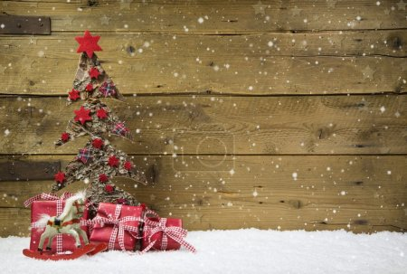 Christmas tree with red presents and snow on wooden snowy backgr