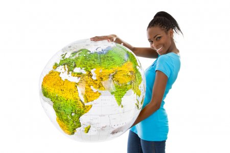 Isolated colored young woman holding a globe in her hands.