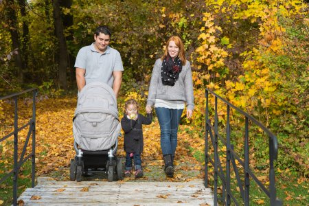 Happy young family in autumn making together a walking tour.
