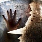 A man behind dirty window in dark background havin...