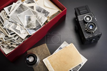 Photo for Retro camera and photos in a box on a gray background - Royalty Free Image