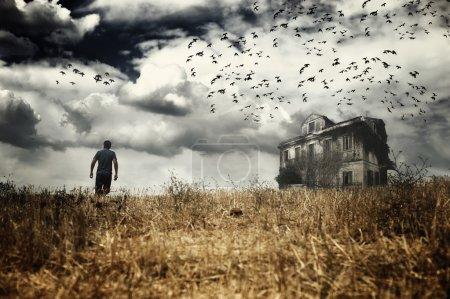 Photo pour Homme marchant dans un champ vers une maison hantée - image libre de droit