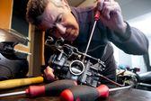 Mecanic repairs a carburetor