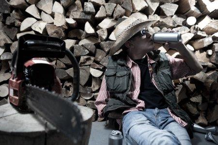 Photo pour Bûcheron avec tronçonneuse ayant un frein avec quelques bières - image libre de droit