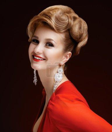 Foto de Retrato de una mujer hermosa y elegante con un vestido rojo con un peinado. labios rojos. pendientes largos. fondo oscuro. - Imagen libre de derechos