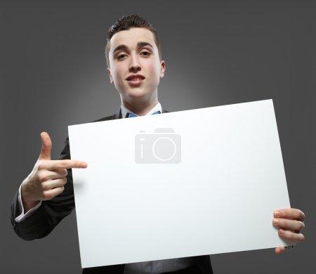 Photo pour Jeune homme tenant un tableau blanc. notion - une démonstration de réalisations en affaires, petites annonces graphiques - image libre de droit