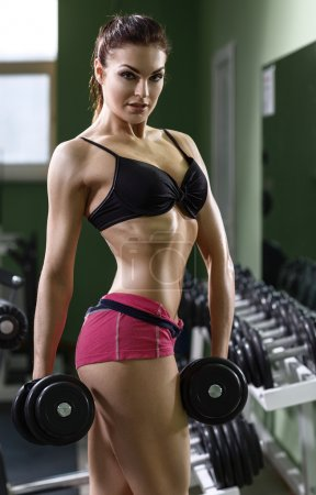 Photo for Woman bodybuilder training with dumbbell. - Royalty Free Image