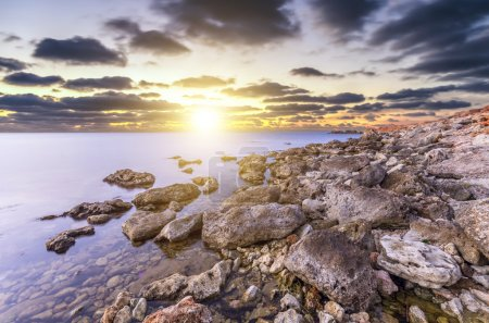 Delightfully bright sunset, the sun's rays excellent coverage of the rocky shore of the ocean