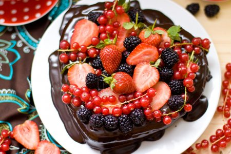Photo for Close up of heart shaped chocolate cake decorated with chocolate frosting, strawberries, blackberries and red currant - Royalty Free Image