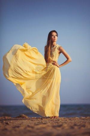 Photo pour Jolie femme en robe de mousseline de soie jaune sur la mer beac - image libre de droit