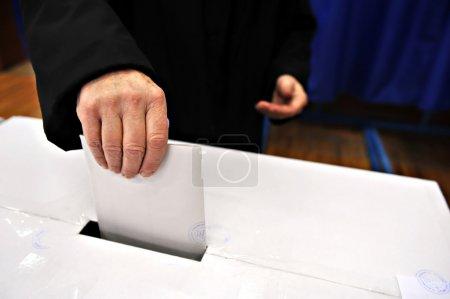 Photo pour Gros plan de la main de l'homme, mettant son vote dans l'urne - image libre de droit