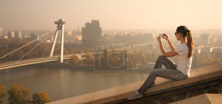 Photo pour Girl sitting over the city over the river and take pictures - image libre de droit