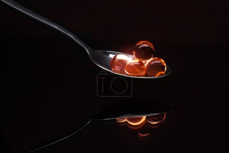 Red caviar on black mirror