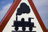 Warnschild, getragen von Bahnübergang ohne Schranken, blauer Himmel mit Wolken