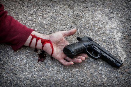 Man with gun in hand bloodstained lies dead in the asphalt murde