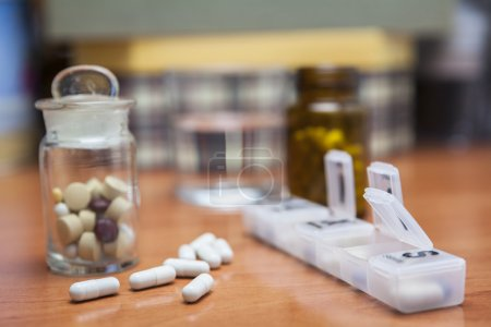 Old bottle of pills along with a few pills above a wooden table