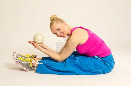 Smiling girl exercising with fitness ball