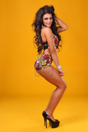 Sexy brunette in swimsuit in a retro style on a yellow background studio shot