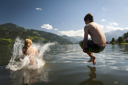 Photo for Girl already in the splashing water and boy in the air while they where jumoing into a lake, with nice nature and mountains in the back - Royalty Free Image