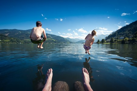 Kids jumping into blue lake on summer day