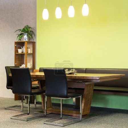 View to wooden table with leather chairs in dining room with illumination