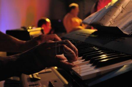 Photo pour Gros plan d'une paire de mains jouant du piano en concert - image libre de droit