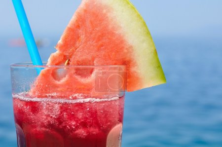 Fresh tropical fruit cocktail with water melon slice on a beach