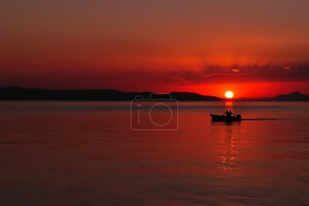 Photo for Silhouette of two people in the boat on the adriatic sea at sunset. Podgora, Croatia - Royalty Free Image