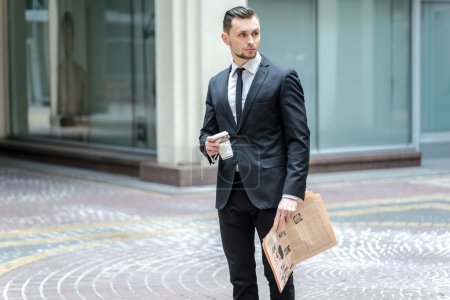 path to success. Confident businessman with coffee and newspaper