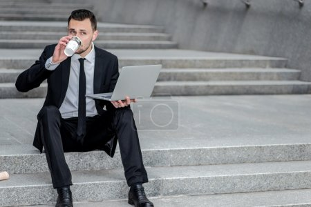 Hot coffee. Young businessman drinking coffee on the street and