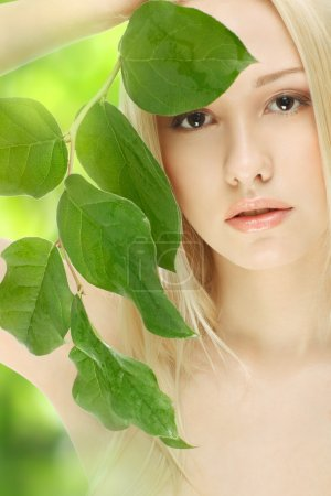 Photo for Closeup portrait of lovely girl covering her face with green sprout over green background - Royalty Free Image