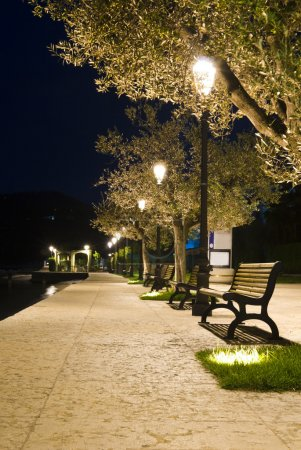 Benches on the pavement in the light of a lantern